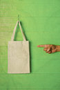 Hand and finger pointing to clothes bag on green Royalty Free Stock Photo