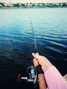 Hand with a fishing rod water over female manicure holding Royalty Free Stock Photography