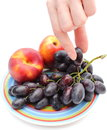 Hand and fruits on colorful plate with grapes nectarines the color isolated white background Royalty Free Stock Images