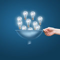 Hand with a funnel and a lot of bulbs, the concept of lots of business ideas