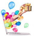 Hand with a gift and laptop balloons come out from screen of computer isolated on white background Royalty Free Stock Photos