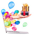 Hand with a gift and laptop balloons come out from screen of computer isolated on white background Royalty Free Stock Image