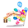 Hand with a gift and laptop balloons come out from screen of computer isolated on white background Stock Photography
