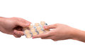 Hand giving lozenges in blister take your pills cropped image of pack of pills passing between hands isolated on white Stock Photography