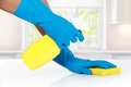 Hand with glove using cleaning sponge to clean up the table Royalty Free Stock Photo