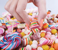 Hand grabbing candy from pile - Overweight problem concept Royalty Free Stock Photo