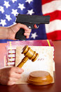 Hand with gun and judges gavel Royalty Free Stock Images