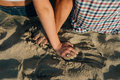 Hands of lovers on sand