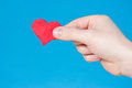 Hand with heart on blue background Stock Images