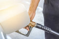 Hand hold fuel nozzle refueling gas pump in service station Royalty Free Stock Photo