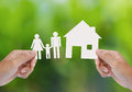 Hand hold house and family on green field Stock Images