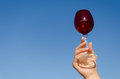 Hand hold red wineglass squirm stem on blue sky female clear with background Stock Photography