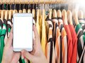 Hand hold smart phone with clothing on hanger in the modern shop