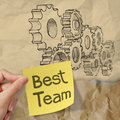 Hand hold sticky note with best team word with gear to success concept on crumpled paper as concept Stock Image
