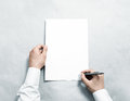 Hand holding blank agreement mockup and signing it arm in shirt hold clear document template mock up contract surface design Royalty Free Stock Photography