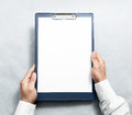 Hand holding blank clipboard with white a4 paper design mockup. Royalty Free Stock Photo
