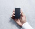 Hand holding blank vertical black business card design mockup.
