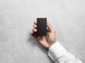 Hand holding blank vertical black business card, design mockup.