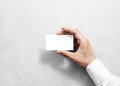 Hand holding blank white business card design mockup.
