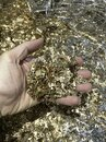 Hand holding bronze scrap cuttings. Royalty Free Stock Photo