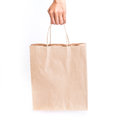 Hand holding brown paper shopping bag on white background Royalty Free Stock Photo