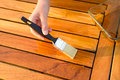 Hand holding a brush applying varnish paint on a wooden garden table Royalty Free Stock Photo