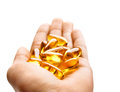 Hand is holding capsules Omega 3 on white background Royalty Free Stock Photo