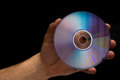 Hand holding a cd male isolated on black background Royalty Free Stock Image
