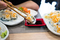 Hand holding Chinese / Japanese sticks and dipping a piece of sushi on a soy sauce, table full of sushi Royalty Free Stock Photo