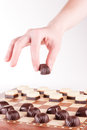 Hand holding chocolate candy over chess board with candies arranged as chess Stock Images