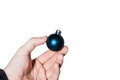 Hand holding a Christmas ball on white background. Royalty Free Stock Photo
