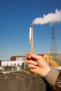 Hand holding a cigarette with an industrial site in the background and blue clear sky Royalty Free Stock Image