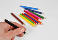 Hand holding crayon and others in the background Royalty Free Stock Image
