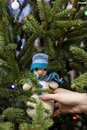 Hand is holding a cute knitted snowman in a hat and scarf on the