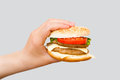 Hand holding delicious fast food cheeseburger on grey background Royalty Free Stock Photo