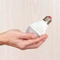 Hand holding ecofriendly led lightbulb on light wood background Royalty Free Stock Photo