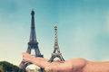 Hand holding an Eiffel tower souvenir toy, real Eiffel tower in the background Royalty Free Stock Photo