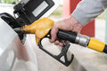 Hand holding fuel pump nozzle and refilling car Royalty Free Stock Photo