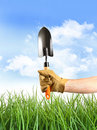 Hand holding garden trowel against blue sky Stock Image