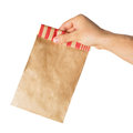 Hand holding or giving a brown paper bag Royalty Free Stock Photography