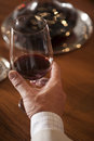 Hand holding glass of red wine on table Stock Photos