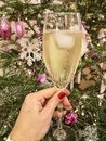 Hand holding a glass of wine against christmas tree