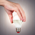 Hand holding a glowing ecofriendly bulb on light wood background Royalty Free Stock Photo
