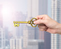Hand holding golden treasure key in Euro symbol shape Royalty Free Stock Photo