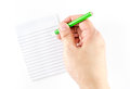 Hand holding green pencil writing on ruled note pad isolated on