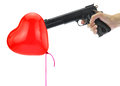 Hand holding at gunpoint a heart balloon isolated on white Royalty Free Stock Photo