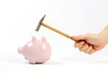 Hand holding hammer and upside down pink piggy bank a a which is raised above a on white background Royalty Free Stock Photography