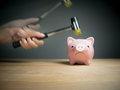 A hand holding a hammer which is raised above a pink sad piggy bank, with a shocked and apprehensive facial expression.