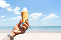 Hand holding ice cream cone on the beach with blue sky Royalty Free Stock Photo