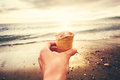 Hand holding ice cream with sea beach sunset on background summer vacations travel lifestyle concept Royalty Free Stock Photo
